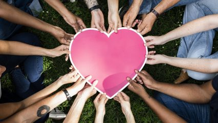 Group of people holding a pink heart icon