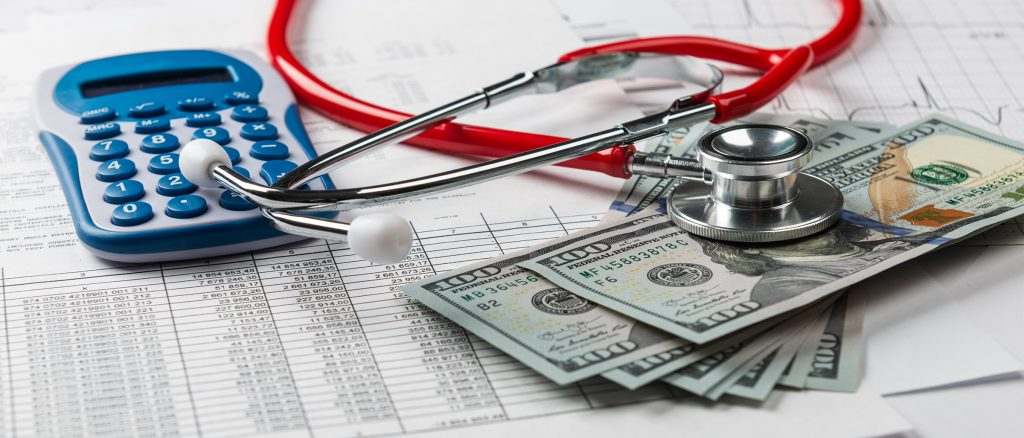 Calculator, Money and stethoscope on paperwork